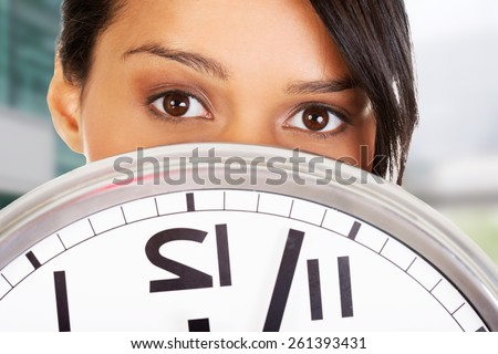 Portrait of shocked woman with clock. - stock photo
