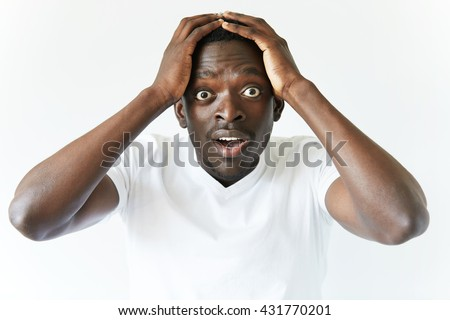 Portrait of shocked young African American man wearing white blank T-shirt looking at the camera in surprise, stunned with some incredible story, holding hands on head. Human expressions and emotions - stock photo