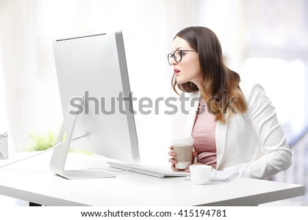Portrait of shocked young businesswoman sitting at desk in front of monitor while working at office.