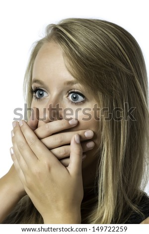 Portrait of shocked young girl who is afraid and keeps up with eyes wide open hand over her mouth, isolated on white background - stock photo