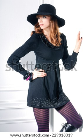 portrait of shot of fashion model with cap in studio - stock photo