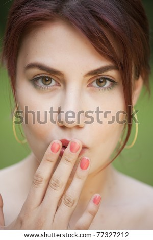 portrait of shy young woman with her hand covering mouth - stock photo