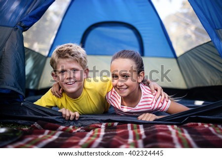 Portrait of siblings embracing each other in a tent