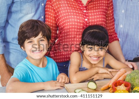 Portrait of siblings with family in kitchen - stock photo