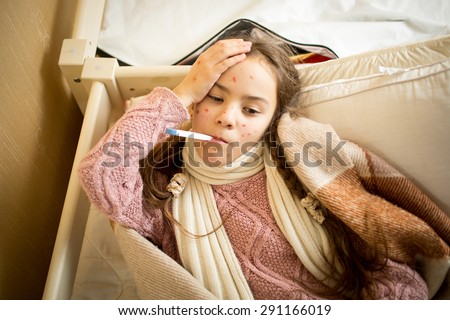 Portrait of sick girl with chickenpox lying in bed and measuring temperature - stock photo