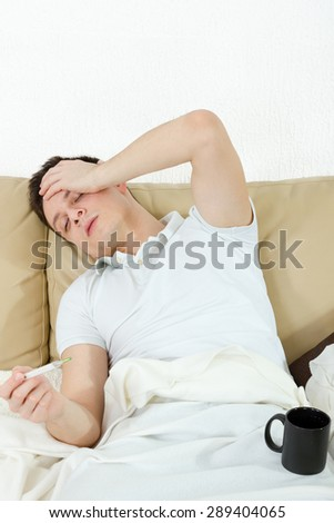 Portrait of sick man in bedroom suffering from influenza measuring temperature with thermometer and drinking tea - stock photo