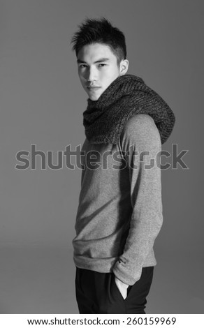 portrait of side view young man with scarf standing with hands in pockets  - stock photo