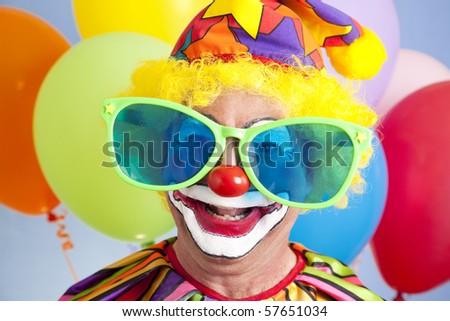 Portrait of silly clown in oversized sunglasses. - stock photo
