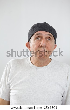 Portrait of simpleminded person wearing a flat cap. - stock photo