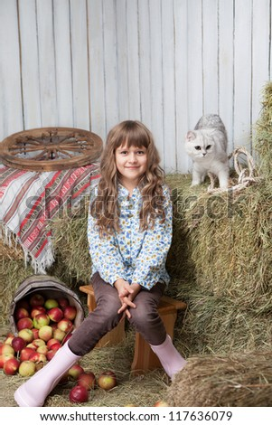 Portrait of sincere little blond girl villager sitting near pail with apples and white cat on hay stack in wooden hayloft - stock photo