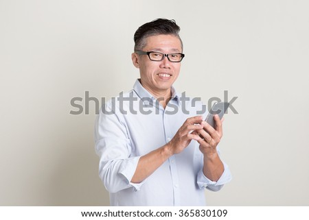 Portrait of single mature 50s Asian man in casual business texting using smartphone and smiling, standing over plain background with shadow. Chinese senior male people. - stock photo