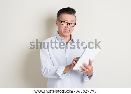 Portrait of single mature 50s Asian man in casual business using digital tablet pc and smiling, standing over plain background with shadow. Chinese senior male people. - stock photo