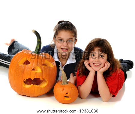 Portrait of sisters posing with the pumpkins they've just carved for Halloween.  Isolated on white.