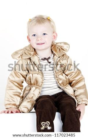 portrait of sitting little girl wearing jacket - stock photo