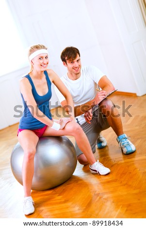 Portrait of sitting on fitness ball slim girl and her personal trainer - stock photo