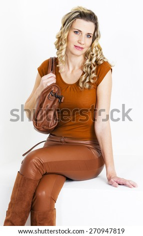 portrait of sitting woman wearing brown clothes and boots with a handbag - stock photo