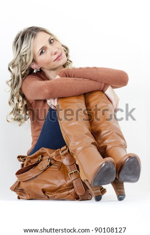 portrait of sitting woman wearing fashionable brown boots with a handbag