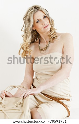portrait of sitting woman wearing summer clothes with a handbag - stock photo