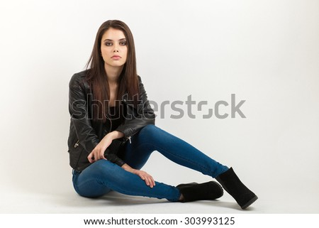 Portrait of sitting young calm beautiful brunette woman posing for model tests against white background - stock photo