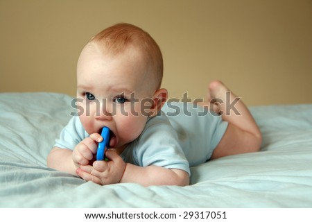 Portrait of six months old sweet baby. A beautiful baby playing with rattle. - stock photo