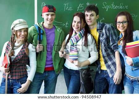 Portrait of six teens in classroom background green board - stock photo