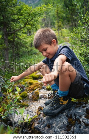 Portrait of six year old boy playing outdoors in the mountains. Dolomites, Italy.