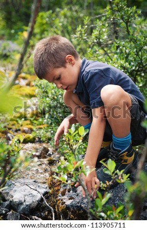 Portrait of six year old boy playing outdoors in the mountains. Dolomites, Italy. - stock photo