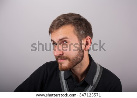 Portrait of skeptical man looking suspicious, some disgust on his face mixed with disapproval isolated on gray  background - stock photo