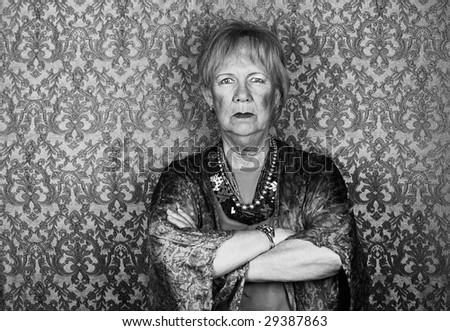 Portrait of skeptical senior woman in front of gold background