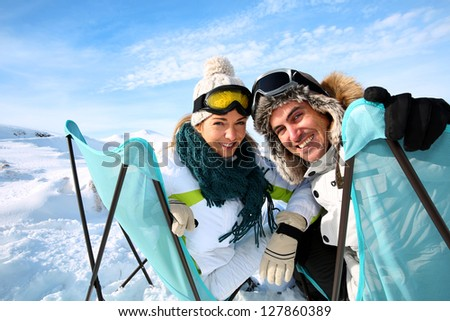 Portrait of skiers sitting in long chairs - stock photo