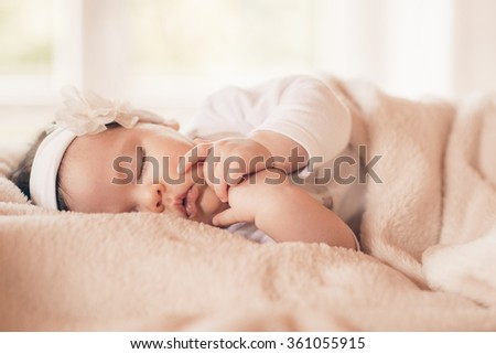 Portrait of sleeping baby in home and window is behind
