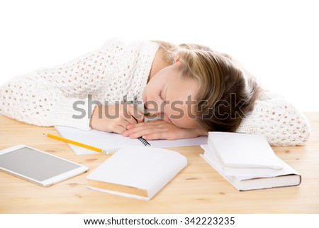Portrait of sleeping beautiful casual caucasian girl wearing white knitted sweater, lying on table, asleep on textbooks while doing homework, studying, studio isolated, white background - stock photo