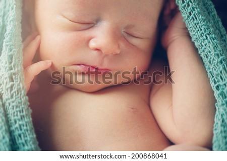 Portrait of Sleeping Newborn Baby in Wrap - stock photo