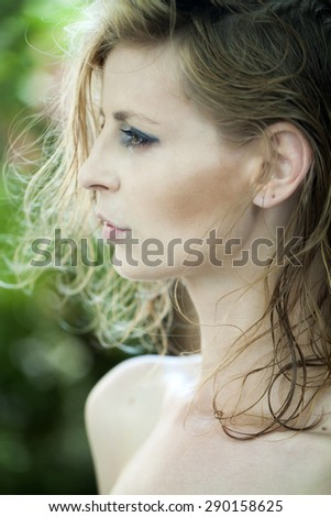 Portrait of slender young woman profile with blonde short hair standing on natural background, vertical picture - stock photo