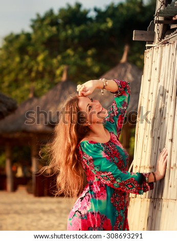 portrait of slim brunette longhaired girl in colorful dress by reed wall against defocused background - stock photo