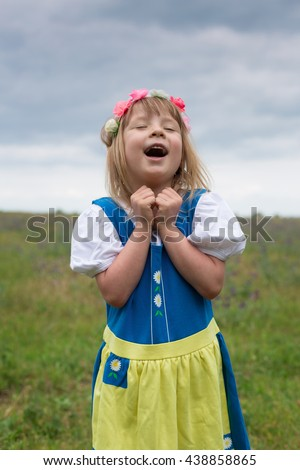 portrait of small adorable blond girl wearing traditional swedish national folk costume in blue and yellow colors on midsummer celebration and singing a song in good mood - stock photo
