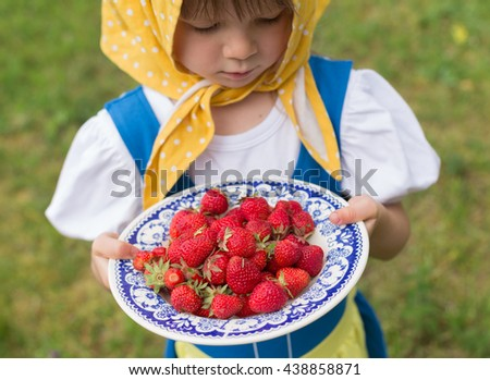portrait of small adorable blond girl wearing traditional swedish national folk costume in blue and yellow colors on midsummer celebration holding plate with fresh strawberries - stock photo