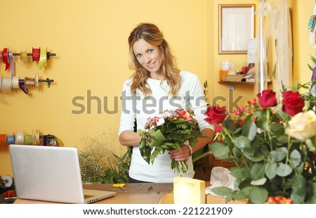 Portrait of small business owner standing and holding flowers in her hand. - stock photo