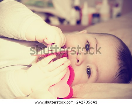 Portrait of small caucasian baby boy lying with toy