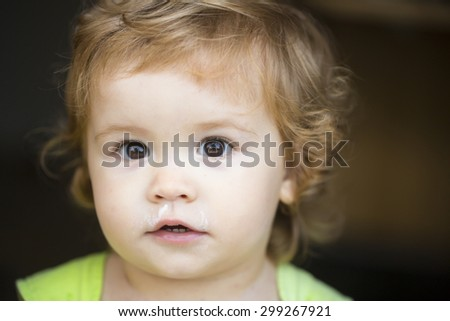 Portrait of small curious sweet male kid with blond curly hair looking forward outdoor on dark background, horizontal picture - stock photo