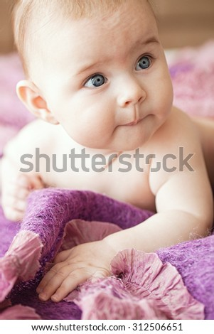 Portrait of small cute girl with blue eyes in her cozy violet bed.  - stock photo