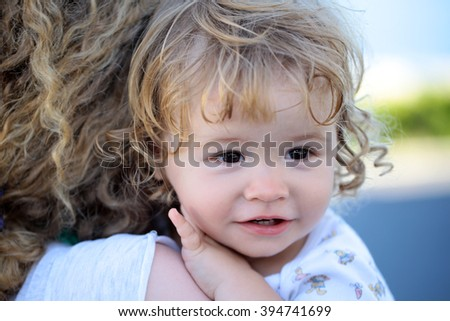 Portrait of small cute serious child boy with blonde curly hair on hands of mother embracing outdoor looking away, horizontal picture - stock photo