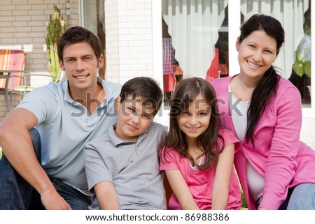 Portrait of small family of four sitting together - Outdoors - stock photo
