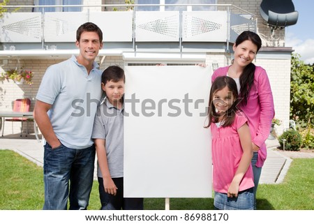 Portrait of small family standing outside with a empty sign board - stock photo