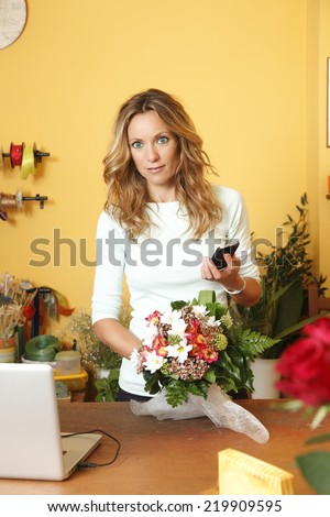 Portrait of small flower shop owner with phone, create a bouquet of flowers. Small business.  - stock photo
