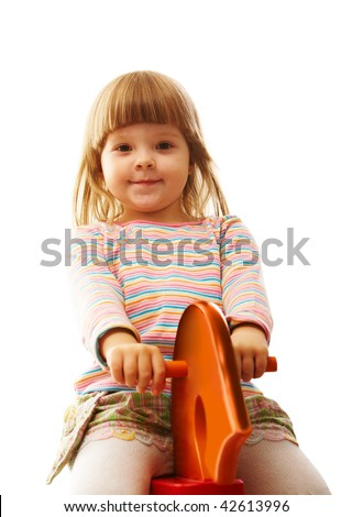 Portrait of small girl looking aside while riding toy horse