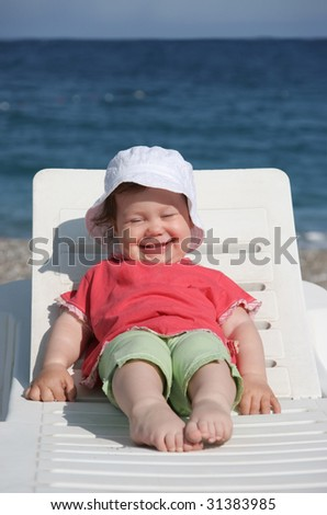 Portrait of small girl lying on deck-chair and enjoying sunny day on beach - stock photo
