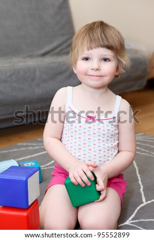 Portrait of small girl playing with bricks on floor