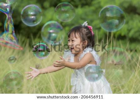 Portrait of small kid playing with soap bubbles.