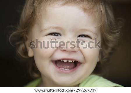 Portrait of small laughing cute male kid with blond curly hair looking forward outdoor on dark background, horizontal picture - stock photo